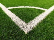 Γωνία παιδικών χαρών ποδοσφαίρου στο τεχνητό πράσινο έδαφος τύρφης με τα χρωματισμένα άσπρα σημάδια γραμμών Στοκ Φωτογραφίες