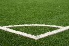 Γωνία παιδικών χαρών ποδοσφαίρου στο τεχνητό πράσινο έδαφος τύρφης με τα χρωματισμένα άσπρα σημάδια γραμμών Αλεσμένο μαύρο λάστιχ Στοκ Εικόνες