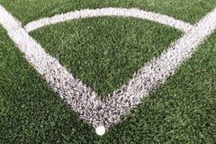 Γωνία παιδικών χαρών ποδοσφαίρου στο τεχνητό πράσινο έδαφος τύρφης με τα χρωματισμένα άσπρα σημάδια γραμμών Αλεσμένο μαύρο λάστιχ Στοκ Εικόνα