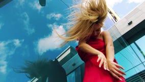 Γωνία που πυροβολείται χαμηλή της χορεύοντας γυναίκας κοντά στην επιφάνεια καθρεφτών που απεικονίζει τα σύννεφα απόθεμα βίντεο