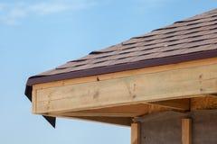 Γωνία του σπιτιού με τις μαρκίζες, ξύλινα ακτίνες και βότσαλα ασφάλτου στεγών στοκ εικόνα
