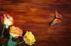 Γωνία φιαγμένη από τριαντάφυλλα και πεταλούδα σε μια ξύλινη επιφάνεια Στοκ Εικόνα