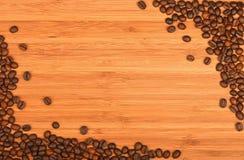 Γωνίες φασολιών καφέ πέρα από το ξύλινο υπόβαθρο μπαμπού Στοκ Εικόνες