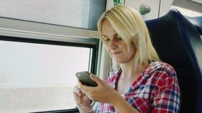 Γύροι οι νέοι γυναικών στο δεύτερο όροφο ενός τραίνου, κάθονται από το παράθυρο Χρησιμοποιήστε ένα smartphone με τα ακουστικά απόθεμα βίντεο