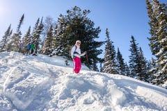 Γύροι σκιέρ γυναικών μέσω του χιονιού σκονών στα βουνά Freeride χειμερινού αθλητισμού Στοκ Φωτογραφία