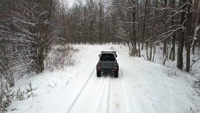 Γύροι SUV 6x6 από το χειμερινό δρόμο στο χιονισμένο δάσος απόθεμα βίντεο
