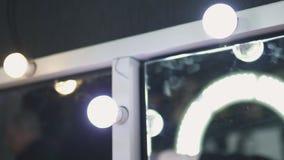 Γύρος καθρεφτών καλλιτεχνών Makeup με τις λάμπες φωτός και circulad τον οδηγημένο λαμπτήρα με τους θολωμένους ανθρώπους που απεικ φιλμ μικρού μήκους