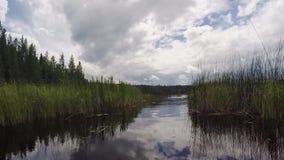 Γύρος κανό κατά μήκος ενός ήρεμου ποταμού με τις αντανακλάσεις σύννεφων απόθεμα βίντεο