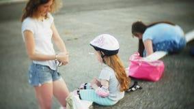 Γύρος Mom και κορών στα σαλάχια κυλίνδρων Κορίτσι που μαθαίνουν στο σαλάχι κυλίνδρων, και πτώσεις Το Mom διδάσκει την κόρη για να απόθεμα βίντεο