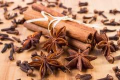 Γλυκάνισο αστεριών, ραβδιά κανέλας και γαρίφαλα στον ξύλινο πίνακα, που καρυκεύει για το μαγείρεμα Στοκ Εικόνες