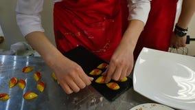 Γλυκά διακοσμητικά θαλασσινά κοχύλια Η γυναίκα βάζει τα γλυκά διακοσμητικά κοχύλια σε έναν δίσκο απόθεμα βίντεο