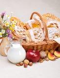 Γλυκά κέικ στη διακόσμηση καλαθιών, φρούτων και γάλακτος στοκ εικόνα
