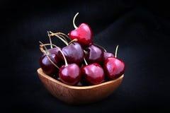 Γλυκά κεράσια στο ξύλινο κύπελλο που απομονώνεται στο μαύρο υπόβαθρο Στοκ Φωτογραφία