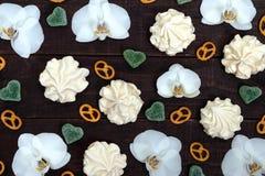 Γλυκά: μαρέγκες και καρδιές ζελατίνας, άσπρα λουλούδια ορχιδεών, αλμυρό Bretzel σε έναν σκοτεινό ξύλινο πίνακα Στοκ Εικόνα