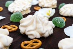 Γλυκά: μαρέγκες και καρδιές ζελατίνας, άσπρα λουλούδια ορχιδεών, αλμυρό Bretzel Στοκ Φωτογραφίες