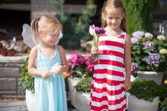 Γλυκά μικρά κορίτσια σε ένα ναυπηγείο χωρών με τα λουλούδια Στοκ φωτογραφία με δικαίωμα ελεύθερης χρήσης