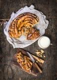 Γλυκά πλεγμένα κέικ και φλυτζάνι του γάλακτος στο σκοτεινό ξύλινο υπόβαθρο Στοκ Εικόνες