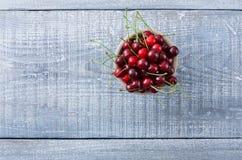Γλυκά φρέσκα κεράσια με τα πράσινα φύλλα στο μπλε αγροτικό ξύλο Στοκ Φωτογραφίες