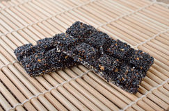 Γλυκαμένος μαύρος φραγμός σουσαμιού στο χαλί μπαμπού στοκ εικόνες