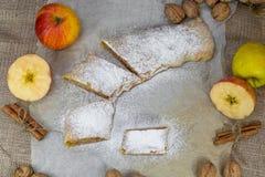 Γλυκαμένο σπιτικό Strudel της Apple σε χαρτί ψησίματος, ξύλο καρυδιάς, Cinnam Στοκ Φωτογραφία