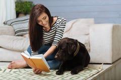 Γλυκιά γυναικεία ανάγνωση φροντίδας για το κατοικίδιο ζώο της Στοκ εικόνα με δικαίωμα ελεύθερης χρήσης