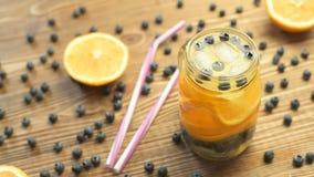 Γλυκιά λεμονάδα με το πορτοκάλι και βακκίνιο σε ένα βάζο φιλμ μικρού μήκους