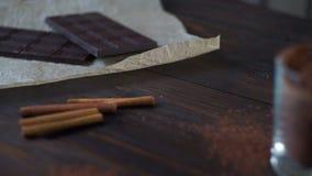 Γλυκιά σοκολάτα με τη σκόνη κακάου στο ξύλινο υπόβαθρο σκοτάδι σοκολάτας ράβδων φιλμ μικρού μήκους