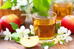 Γλυκοί χυμός μήλων, μήλα και λουλούδια στον πίνακα Στοκ Φωτογραφία