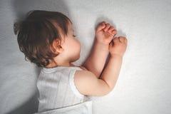 Γλυκός ύπνος μωρών σε ένα άσπρο υπόβαθρο κρεβατιών Στοκ Εικόνες