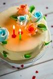 Γλυκό κέικ γενεθλίων που διακοσμείται με τα κεριά και τα τριαντάφυλλα Στοκ Εικόνες