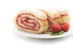 Γλυκό κέικ ρόλων με τη μαρμελάδα και τα μούρα σμέουρων, που απομονώνονται σε ένα wh Στοκ Φωτογραφία