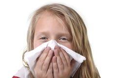 Γλυκό και χαριτωμένο μικρό κορίτσι ξανθών μαλλιών που φυσά τη μύτη της με τον ιστό εγγράφου που έχει ένα κρύο που αισθάνεται άρρω στοκ φωτογραφίες με δικαίωμα ελεύθερης χρήσης