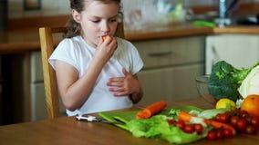 Γλυκό κορίτσι που τρώει τα καρότα στην κουζίνα απόθεμα βίντεο