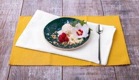 Γλυκό κρύο επιδόρπιο και ένα άσπρο λουλούδι σε ένα ζωηρόχρωμο επιτραπέζιο υπόβαθρο Παγωτό βανίλιας με τα σμέουρα, τη μέντα και τα Στοκ Εικόνα