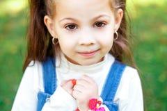 Γλυκό μικρό κορίτσι υπαίθρια με τη σγουρή τρίχα σε δύο μακριές ουρές, κινηματογράφηση σε πρώτο πλάνο portret στοκ εικόνα