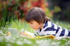 Γλυκό μικρό παιδί, που ξαπλώνει την άνοιξη κήπος λουλουδιών, που παίζει επάνω Στοκ φωτογραφία με δικαίωμα ελεύθερης χρήσης