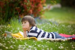 Γλυκό μικρό παιδί, που ξαπλώνει την άνοιξη κήπος λουλουδιών, που παίζει επάνω Στοκ εικόνα με δικαίωμα ελεύθερης χρήσης