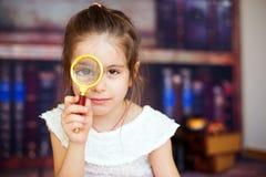 Γλυκό παιδί, κορίτσι, που παίζει με μια ενίσχυση - γυαλί Στοκ Φωτογραφία
