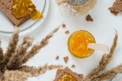 Γλυκό πρόχειρο φαγητό ή πρόγευμα με την πορτοκαλιά μαρμελάδα στο βάζο γυαλιού, σουηδικές κροτίδες ψωμιού σίκαλης τραγανές με την  Στοκ φωτογραφία με δικαίωμα ελεύθερης χρήσης