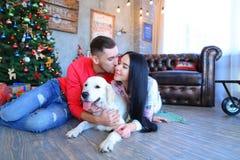 Γλυκό φίλημα ζευγών, τοποθέτηση και χαμόγελο στη κάμερα, εκτός από το σκυλί ι Στοκ Εικόνα