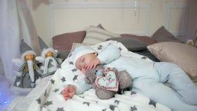 Γλυκό χαριτωμένο αγόρι ονείρου, παιδί που αγκαλιάζει ένα παιχνίδι ενώ οι κοισμένος, μικροί ύπνοι παιδιών, μωρό που βρίσκονται στο απόθεμα βίντεο