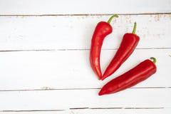 Γλυκό kapi κόκκινων πιπεριών, τρία πιπέρια στον άσπρο ξύλινο πίνακα Στοκ εικόνες με δικαίωμα ελεύθερης χρήσης
