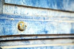 γδυμένος στην μπλε ξύλινη πόρτα και το σκουριασμένο καρφί στοκ εικόνα