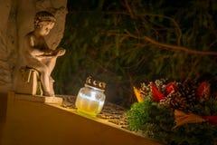 Γλυπτική, κερί και στεφάνι ταφοπέτρων στον τάφο Στοκ Εικόνα