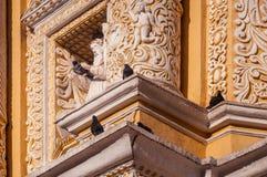 Γλυπτό που περιβάλλεται από τα περιστέρια ο την όμορφη πρόσοψη της εκκλησίας Λα Merced στη Αντίγκουα Στοκ Φωτογραφία
