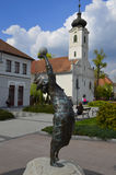 Γλυπτό στο κέντρο Gödöllö με την εκκλησία Στοκ Εικόνα