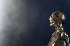 Γλυπτό του αρρενωπού ρομπότ σε ένα σκούρο μπλε υπόβαθρο Στοκ Φωτογραφίες