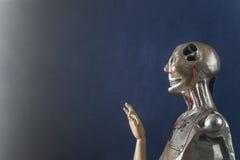 Γλυπτό του αρρενωπού ρομπότ σε ένα σκούρο μπλε υπόβαθρο Στοκ εικόνα με δικαίωμα ελεύθερης χρήσης