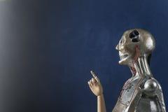 Γλυπτό του αρρενωπού ρομπότ σε ένα σκούρο μπλε υπόβαθρο Στοκ εικόνες με δικαίωμα ελεύθερης χρήσης