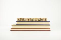 Γλωσσική λέξη αφρικανολλανδικής στα ξύλινα γραμματόσημα και τα βιβλία στοκ φωτογραφίες